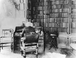 Frederick Douglass reading at his desk in Washington, D.C.